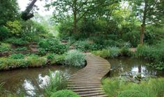 A sinuous wood bridge curves across a pond in a country garden at Stonehealed Farm in East Sussex. from Period Living