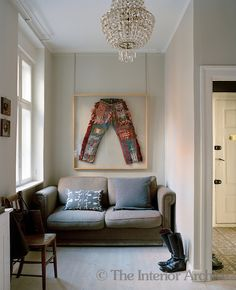 A two-seater sofa fills this narrow area in the living room beneath a framed pair of couture trousers