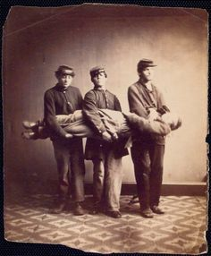 ca. 1861-1872, [Three soldiers carry a fourth to demonstrate one stage of the correct method to raise a soldier from a reclining position for carrying], United States Sanitary Commission