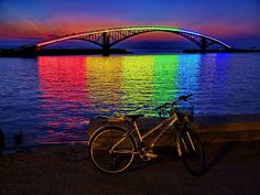 The Xiying Rainbow Bridge is an elevated pedestrian walkway located in Magong, Penghu County in Taiwan. The bridge is lined with a thin neon band that reflects a rainbow onto the water's surface below at night. Love Rainbow, Over The Rainbow, Rainbow Colors, Rainbow Things, Rainbow Light, White Rainbow, Ouvrages D'art, Somewhere Over, To Infinity And Beyond