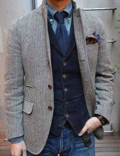 Herringbone tweed blazer layered over unstructured navy jacket and denim shirt.