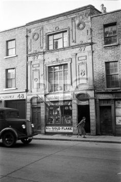 An exterior view of 47 North King Street, Dublin city, in 1952 or 1953. P Foley, tobacconist, was located here at the time this picture was taken. Note the elaborate decorative elements on the building. W Murphy's chemists is partly visible at number 48. A woman using a crutch can be seen passing by Foley's. Collection RTÉ Johnson Collection Photographer Johnson, Nevill