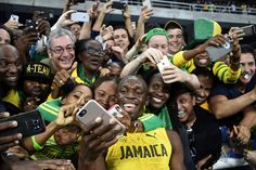 Jamaica's Usain Bolt takes selfie photos as he celebrates with fans after winning the Men's 200m Final at the Rio 2016 Olympic Games in Rio de Janeiro on August 18, 2016.