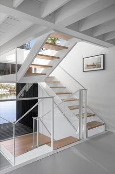 A white staircase in this modern float home matches the walls and ceiling, connects the various levels of the float home, and adds a warm wood element to the space.