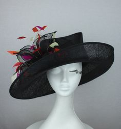 Large black sinamay hat with mad hatter crown and brim with pink orange and white feather and sinamay accents.