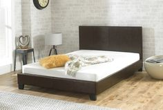 The Valencia in brown is a sleek, modern-looking bed frame upholstered in faux leather.