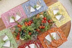 Uma mesa posta no jardim para servir pizza com jogos americanos com estampas de bandana, arranjo com legumes e verduras e outros detalhes que amamos!