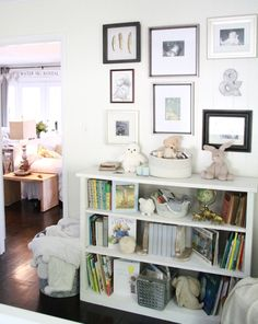 Love the styling of this gallery wall + bookshelves! (The framed gold-dipped feathers are to. die. for.) #nursery #nurserydecor #gallerywall
