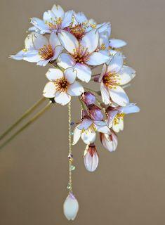 Kanzashi é um tradicional ornamento de cabelo no Japão, apesar de existir há milhares de anos, o seu uso de popularizou em meados de 1800. O enfeite era usado geralmente em ocasiões especiais, acompanhado pelo quimono. Com a modernidade, essa tradição ficou um pouco esquecida, mas o artista japonês Sakae ainda cria artesanalemente, esses delicados ornamentos florais em resina, as flores são belíssimas e transmitem delicadeza, feminilidade e uma certa fragilidade.