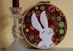 Un cercle de broderie joliment décoré avec un tissu pétillant et un petit lapin blanc en feutrine brodé.