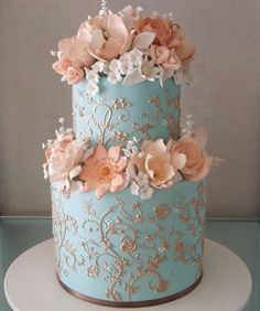 A pretty blue wedding cake with pink flowers and accents.