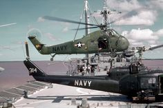 Sikorsky H-34 Choctaw landing beside a Bell UH-1 Huey of the Helicopter Attack (Light) Squadron 3, or HA(L)-3 Seawolves, on the USS Garrett County.