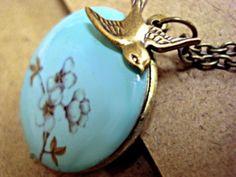Blütenzweig- türkis/bronze Medaillonkette. Ein altgolden farbiges Medaillon habe ich auf der Vorderseite türkis emailliert und dann den zarten Blütenzweig aufgetragen.  Eine kleine Schwalbe fliegt darauf zu. Innen und auf der Rückseite ist das Medaillon altgolden bzw. bronzefarben. Hinein passen 2 Fotos. Die passende Kette ist mittellang mit Verschluß.