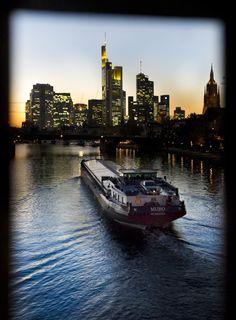 Durch ein Geländer fotografiert, ist die Skyline Frankfurts einmal anders zu sehen, davor fährt ein Schiff.