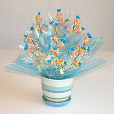 Materials used: a flowerpot, Dubble Bubble Gum, blue cellophane, polka dot cellophane, floral foam, blue plastic grass or blue shredded paper, stem wire (16 or 18 ga), yellow curling ribbon, scotch tape, glue dots, and tools (scissors, serrated knife, and wire cutters).