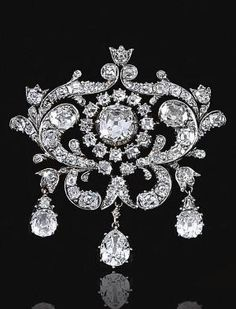 THE ESTATE OF CHRISTIAN, LADY HESKETH Diamond brooch, mid century.The central old-mine diamond in a cut-down collet within open work surrounds designed as foliate scrolls set with old-mine diamonds, suspending three pear-shaped diamond drops Diamond Earing, Diamond Brooch, Diamond Jewelry, Amethyst Jewelry, Do It Yourself Jewelry, Do It Yourself Fashion, Victorian Jewelry, Antique Jewelry, Vintage Jewelry