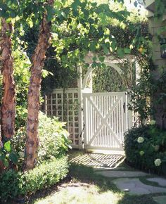 Garden gate | Schuyler Samperton Interior Design.  I like where the tree is in comparison to the house and the path to the gate and the date itself. It's a really nice layout.