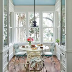 The ceiling in this breakfast room is painted blue, a decision inspired by the superstition that the color keeps evil away.