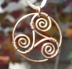 Round copper pendant with a hand formed and hammered triple spiral.    Sometimes called the triskele, the triple spiral is originally from
