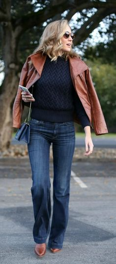 navy cable-knit sweater, dark wash flare leg jeans, cognac leather moto jacket, pointy toe booties + blue handbag