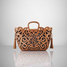 Laser-cut leather defines our Vachetta Scroll Tote, which is crafted in Italy and has a spacious silhouette and a full interior lining