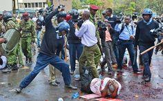"""KENYA, Nairobi. Un policier kenyan frappe un manifestant au sol lors d'une manifestation contre le gouvernement pour réclamer des augmentations de salaires, le 14 mai 2013. Les manifestants ont libéré deux douzaines de porcelets devant le parlement kenyan pour dénoncer la gourmandise des parlementaires du pays, qu'ils accusent de se """"gaver comme des porcs"""". AFP/Carl de Souza"""