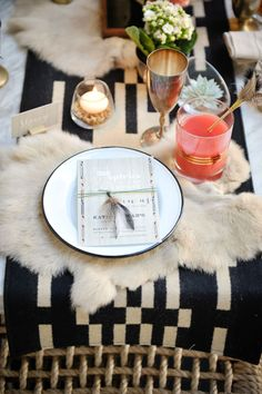 Feather tie on wedding menu with sheepskin & geometric table runner. Feather cocktail stir stick, and gold rimmed glasses   Half Full Photography