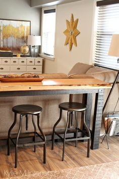 Decorating idea for family or media room. Live edge wood console table with stools behind the couch or sectional. Kylie M Interiors
