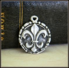 """Who doesn't love a Fleur de Lis? Inspired by my sweet friend from New Orleans, this pendant is handcrafted from a detail mold, fired then finished with a patina process to add the lovely antiqued & weathered affect. 100% fine silver handcrafted, fired, polished patina antiqued finish 16"""" chain included, unless otherwise noted in your order for 18"""" chain"""