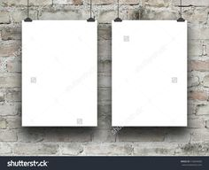 Two blank frames hanged by clips against weathered brick wall background