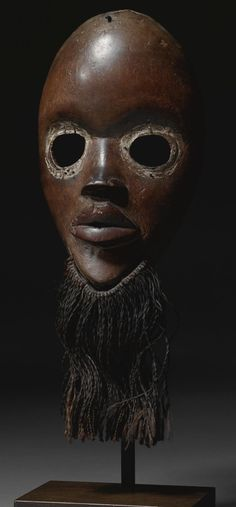 A FINE DAN MASK, IVORY COAST.  of delicate proportions, the sensitive face with a fiber beard attached to the pointed chin beneath the full, slightly parted protruding lips and small nose framed by circular eyes beneath a gently sloping forehead; varied brown patina with traces of white pigment around the eyes.  height (of mask) 9 1/4 in. 23.5cm