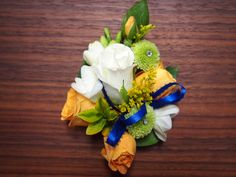 Prom Corsage and matching boutonniere for a royal blue dress, using white and yellow roses, apple green pin cushion mums, white freesia, fun greens and a mixture of textures with ribbons and fillers.   www.urbanelementsinteriorspace.com Portland, OR  97223