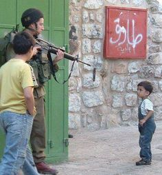 An Israeli defense forces soldier points his gun at a Palestinian boy.