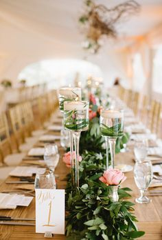 Romantic centerpiece of soft pink roses, dark greenery, and tall pillar candles