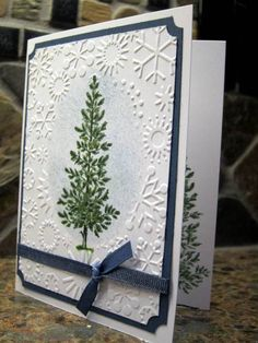 handmade Christmas card ... evergreen tree ...  snowflake embossing folder with created oval flat space for stamping ... blue mat and ribbon ... like it!!