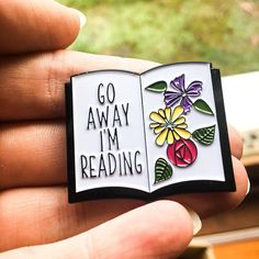 Inspired by our most popular necklace design, we are now proud to bring you our Go Away Im Reading enamel pin. Featuring a floral design and the phrase Go Away Im Reading on an open book. This pin has a clasp back to ensure it does not fall off so you can show off your love of books in