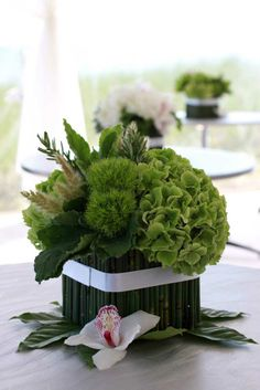 lush green beachfront cocktail table arrangement with hydrangea, green trick dianthus, scented geranium, fresh rosemary, bunnytail grass and snake grass wrap with a white cymbidium orchid accent