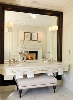 Stunning Bathroom. Love the Large mirror, beautiful vanity with towel racks on the front, lighting on the mirror, bench under sink, fireplace seen in the mirror, built-in cabintery to the right, etc...