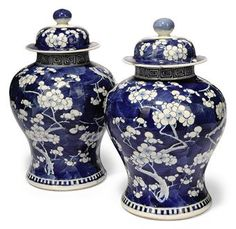A PAIR OF CHINESE BLUE AND WHITE PRUNUS VASES AND COVERS  19TH CENTURY  Each painted with blossoming prunus branches issuing from the top and the base, Kangxi four-character mark to the base