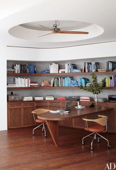Architect Charles Gwathmey's signature curves distinguish his St. Barts home office and its sucupira-wood desk, designed by Kang Chang and fabricated on the island. The swivel chairs are by Hans J. Wegner from DK Vogue, and the ceiling fan is by Boffi.