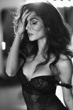 Brunette model in lacy black lingerie sliding off shoulder