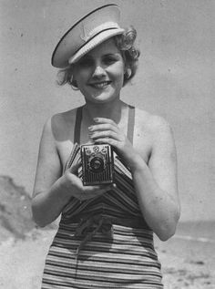 Box Brownie camera held by pretty young lady wearing a bathing suit and hat.