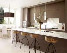 Warm twist on modern style. Carrara marble backsplash, chocolate brown cabinetry & rustic-looking iron & wood barstools.