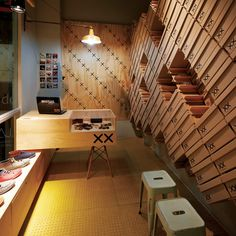 Footware store interior covered with stacked shoe boxes by Move Architects