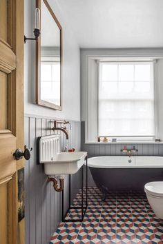 A rolltop tub from the Cast Iron Bath Co sits on custom-coloured encaustic tiles, and the walls are painted in a gentle grey