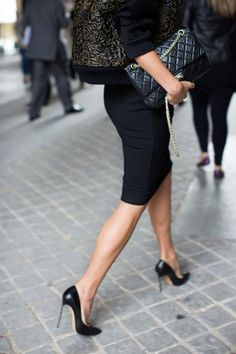 Black pencil skirt with black stiletto heels.  I love the wide, cropped cut of her 3/4 sleeve jacket.