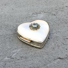 Welcome to Cofflete Art. Here we have something new to our shop. We have never had anything like this in our stock before! This is a very small pill box in the shape of a heart made of sterling grade silver and mother of pearl. The base is silver. It carries the full European hallmarks