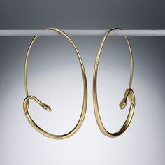 """A pair of 18K yellow gold large snake hoops with diamond eyes. Total length 2"""" x 1 3/8"""" wide."""