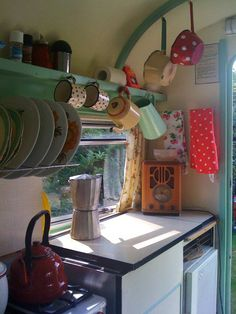 Interior of vintage camper RV green and cream and aqua. Enamelware is cute! And love the antique radio.
