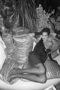 A glamorous woman reclines on glittery cushions at Ku, the world's largest outdoor discotheque, built around an Olympic sized swimming pool ...
